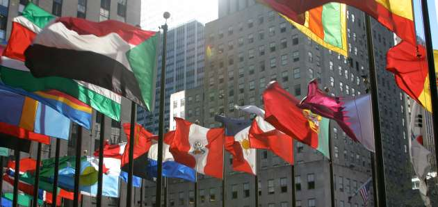 International flags fly in a circle surrounded by city buildings.